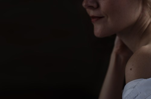 Sensual close up portrait of beautiful young lady relaxing at the window. female shoulder close up. hard shadows. banner